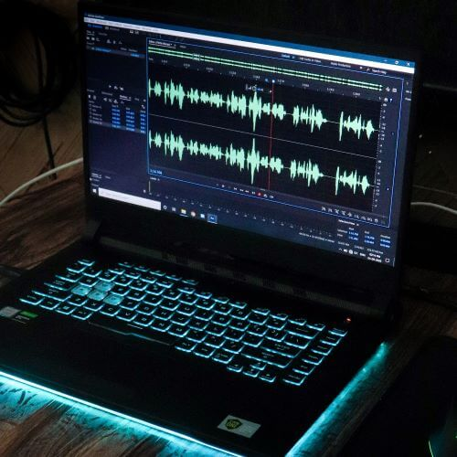 Laptop with media editing software showing sound waves.