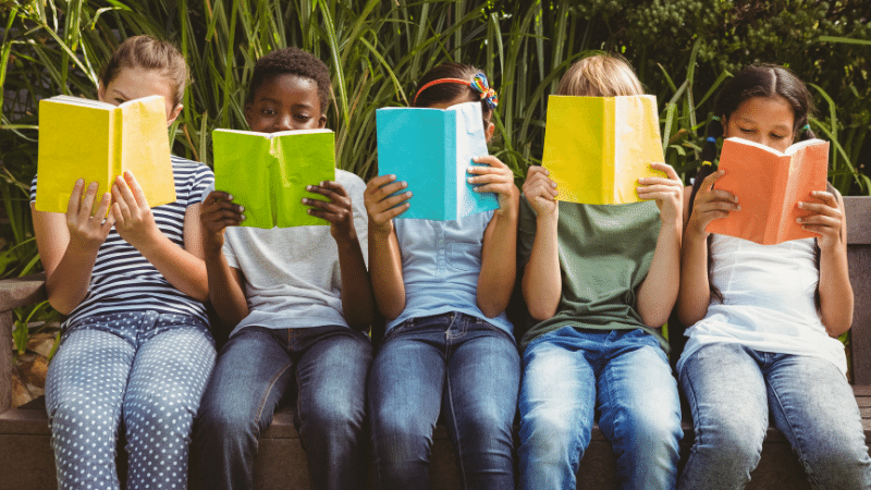Children sat on a park bench reading #WorldKidLit